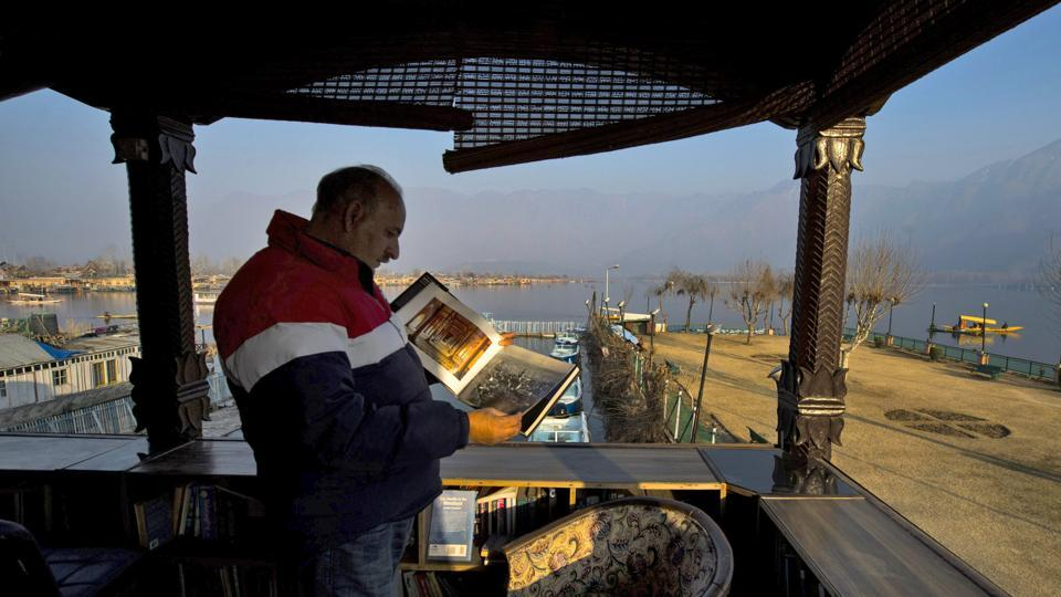 A reader leafs through a book at a store at Dal in Srinagar on Sunday. Gulshan Books, with collection of 80,000 books, was recently included in Limca Book of Records for being the only library in the country to be setup on a lake. (PTI)