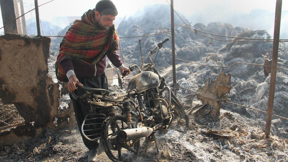 A villager looks at his charred motorcycle after heavy shelling by Pakistani forces, at the border village of Jora Farm in Jammu on Sunday. (PTI)