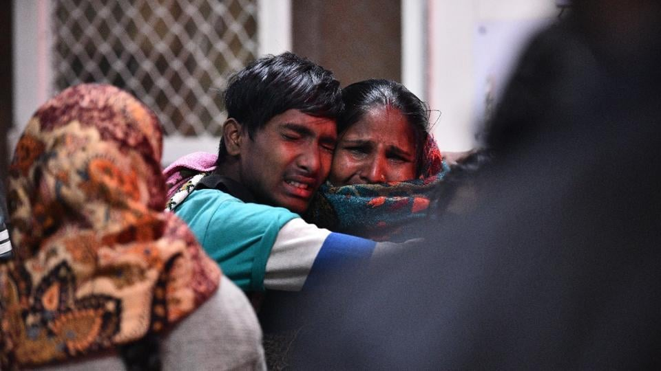 People react as they mourn the death of relatives after a major fire broke at a three-storey factory in north Delhi's Bawana Industrial Area on Saturday. (Sanchit Khanna / HT Photo)