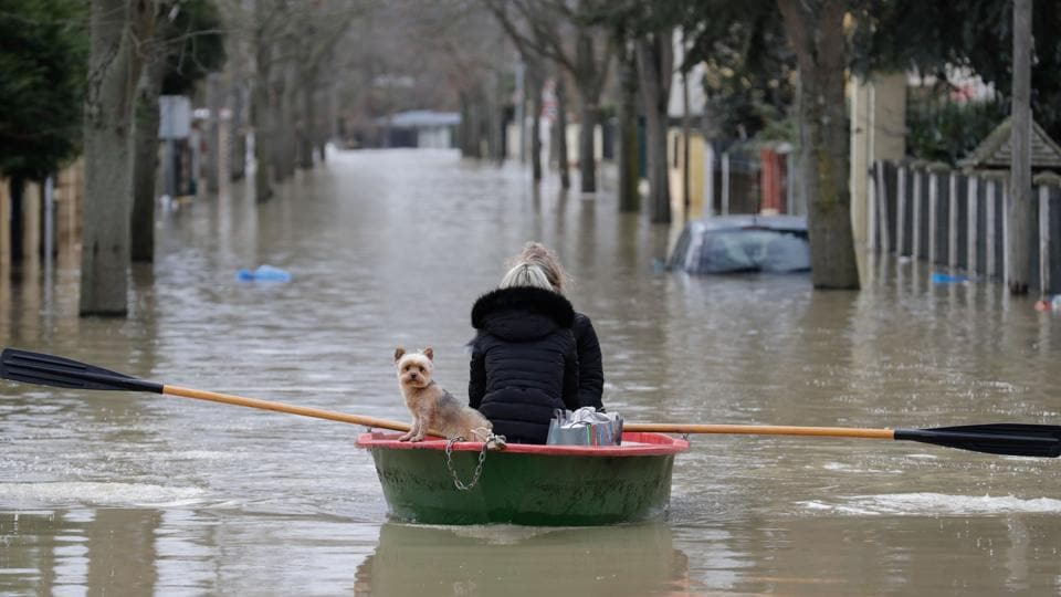Local residents and their dog go down a flooded street in a rowboat in Villeneuve-Saint-Georges on January 24, 2018. France braced for floods on January 23 as the Rhine threatened to overflow and the rapidly rising Seine forced Paris authorities to halt trains on a busy commuter line. Heavy rains have lashed France for days, leaving 30 departments across the country on flood alert. (Thomas Samson / AFP)