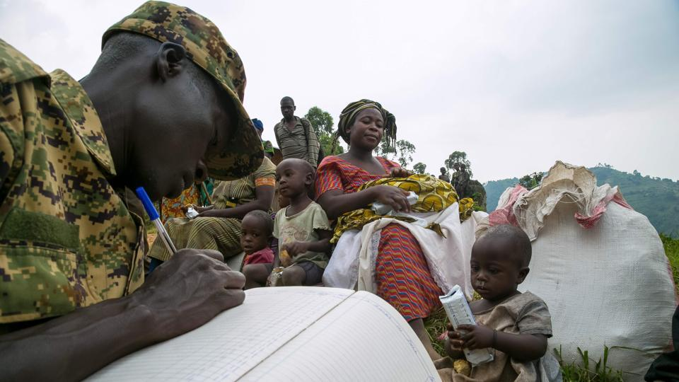 People are registered by an Ugandan soldier after they crossed the border from the Democratic Republic of Congo to become refugees at Nteko village in western Uganda on January 24, 2018. Since last December, about 300 Congolese people per day have been fleeing from the Mai Mai militias' attacks in the Kivu region of the eastern part of DRC to this border area. (Sumy Sadurni / AFP)