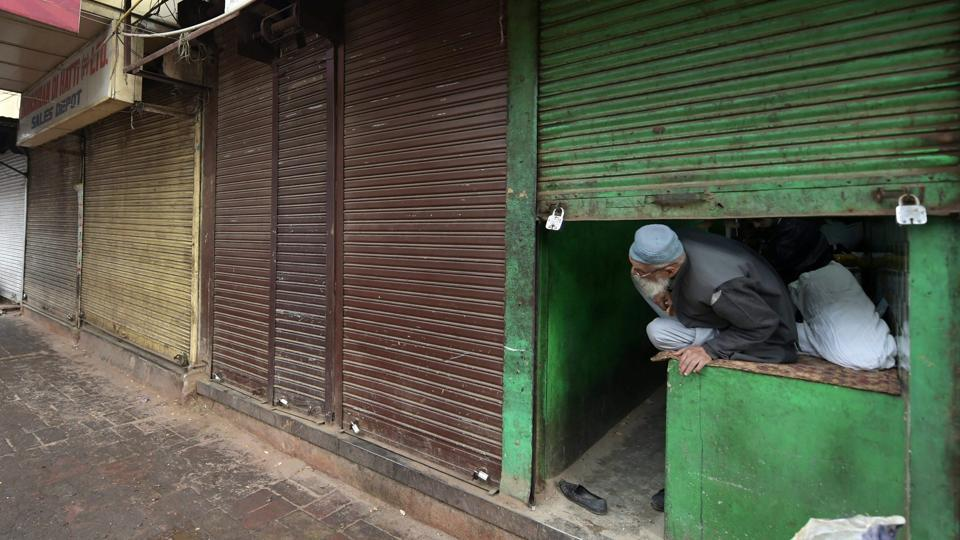 A shopkeeper looks out from his half-shuttered shop at Khari Baoli market during the traders' day-long bandh called over the ongoing sealing of business establishments across the city, on Tuesday.  (PTI)