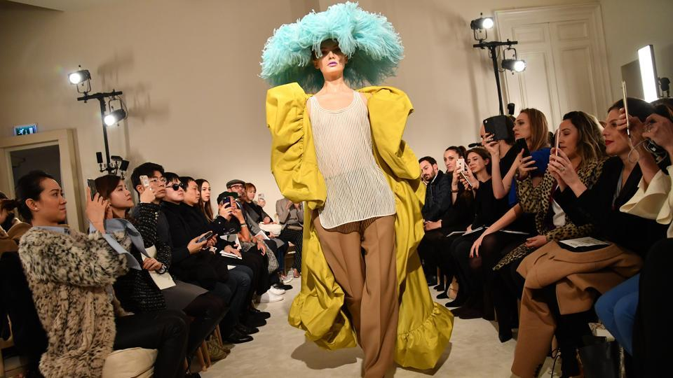 Pierpaolo Piccioli's Valentino presentation opened to a wild clash of colours with a yellow faille coat, over brown work trousers and a simple tank. The giant aquamarine ostrich feather saucer hat gliding down the ramp as onlookers snapped away.  (Pascal Le Segretain / Getty Images)