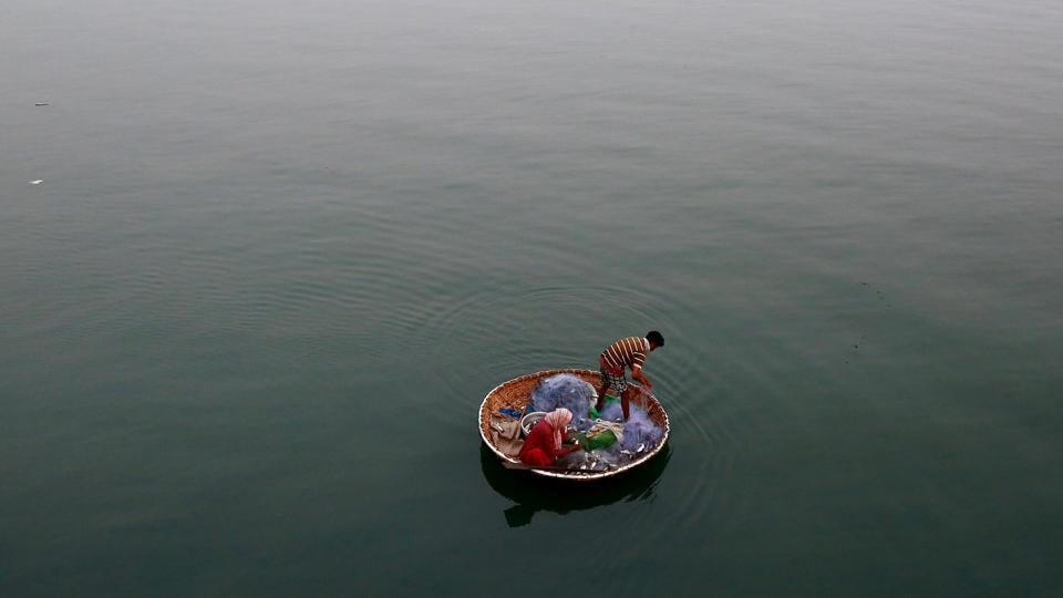 A fisherman and his wife attempt to lure in a catch in the waters of Vembanad Lake in Kochi on Wednesday. (Sivaram V  / REUTERS)