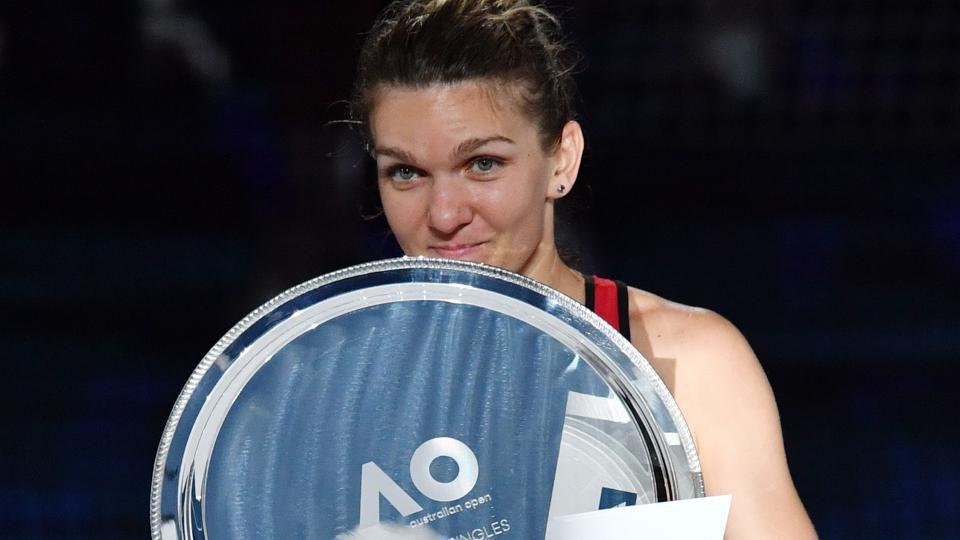 Simona Halep holds up her runners-up trophy during the awards ceremony after the loss against Caroline Wozniacki in the women's singles final of the Australian Open tennis tournament in Melbourne on Saturday.