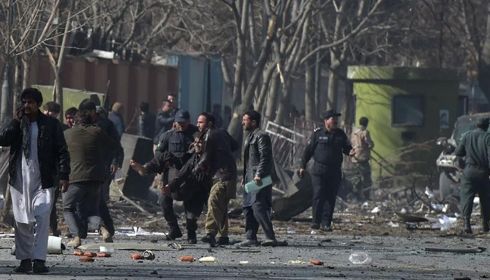 Afghan volunteers and policemen help wounded at the scene of a car bomb exploded in front of the old Interior Ministry building in Kabul on January 27, 2018.