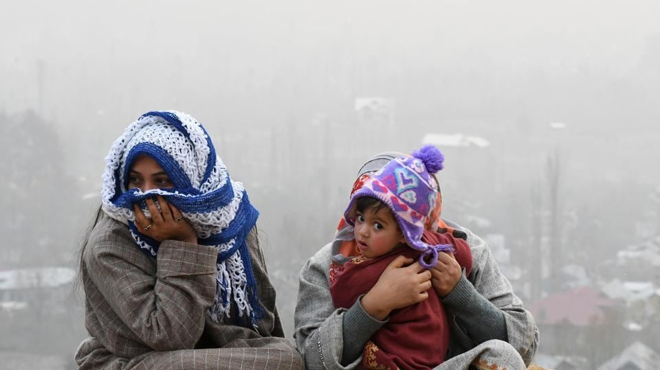 A Kashmiri family sits on the top of the hill in the outskirts of Srinagar on November 29, 2017.