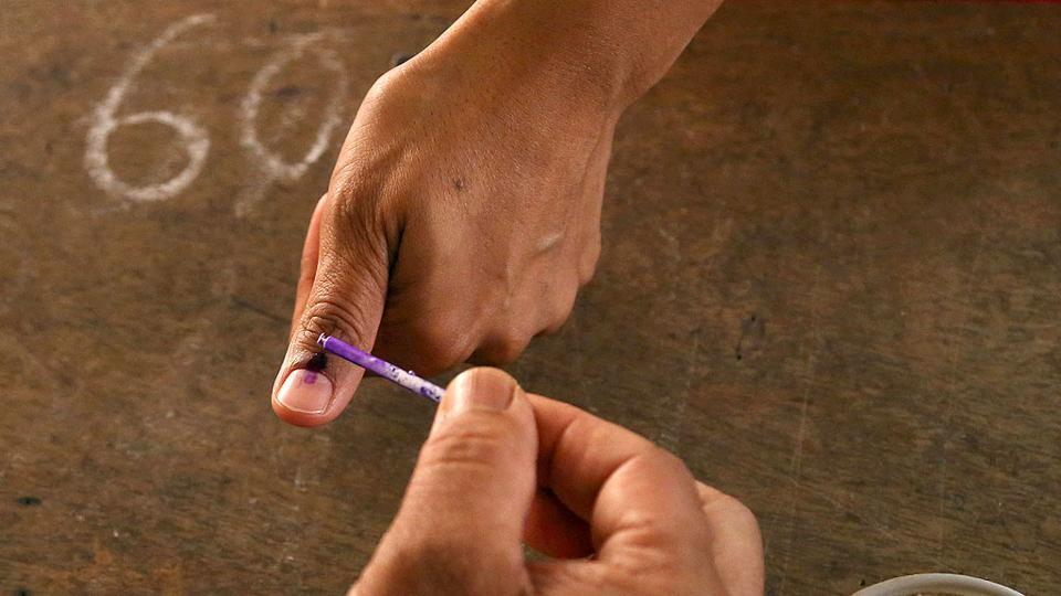 A polling officer marks the finger of a voter with indelible ink at a polling station in Bangalore. (AP Photo)