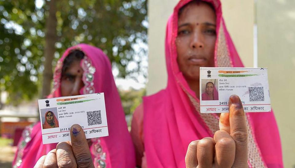 Voters display their Aadhaar cards and finger marked with indelible ink after casting their vote during Ajmer by-election on Monday.