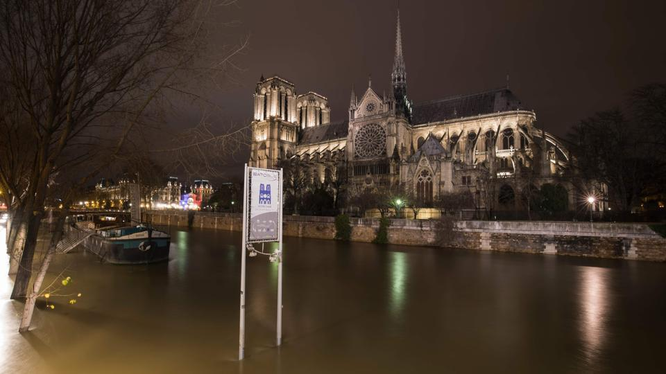 A picture taken on the night of January 28, 2018 in Paris shows the flooded banks of the Seine river near Notre-Dame Cathedral.