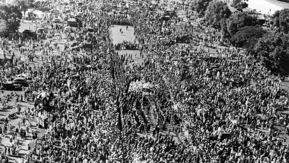 A crowd watches Mahatma Gandhi's funeral procession make its was to Rajghat in Delhi. Large gatherings offered continual prayers beginning from the procession to Rajghat, till February 11, 1948 until the last of Gandhi's ashes had been collected. (Fox Photos / Getty Images)