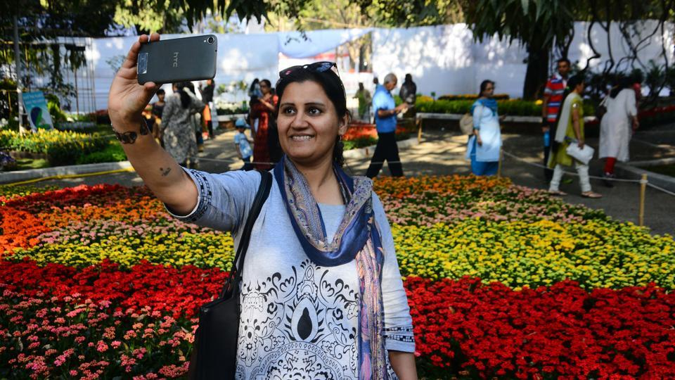 A woman takes a selfie with the decorated flowers at a flower show held in Empress Garden on Thursday, January 25. Families came in large numbers to see the beautiful floral decorations and set of exotic flowers at the show on January 26. (Shankar Narayan/HT PHOTO)