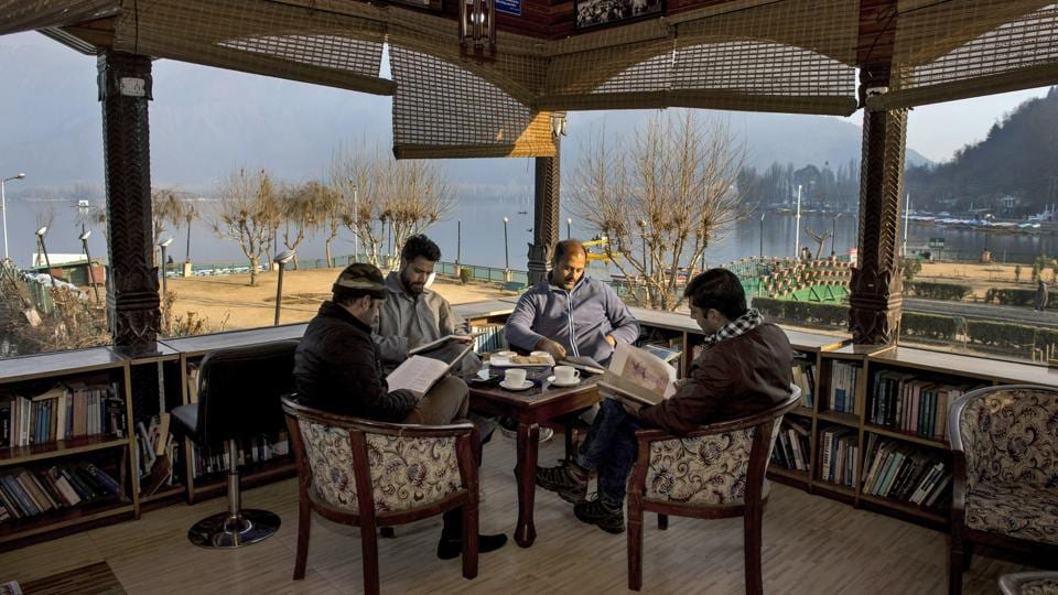 Readers flip through their books with the scenic Dal Lake in the backdrop at Nehru Park in Srinagar. Gulshan Books Kashmir, a bookstore with its collection of 80,000 titles, was recently included in the 2018 Limca Book of Records for being the only library in the country set on a lake. (S Irfan / PTI)