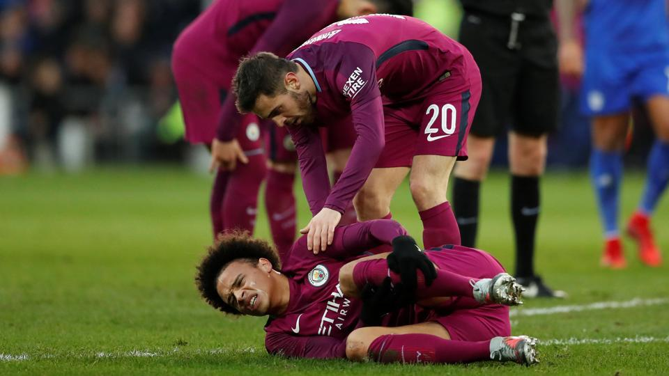 Manchester City's Leroy Sane reacts after sustaining an injury as Bernardo Silva looks on during  their FA Cup clash against Cardiff City.