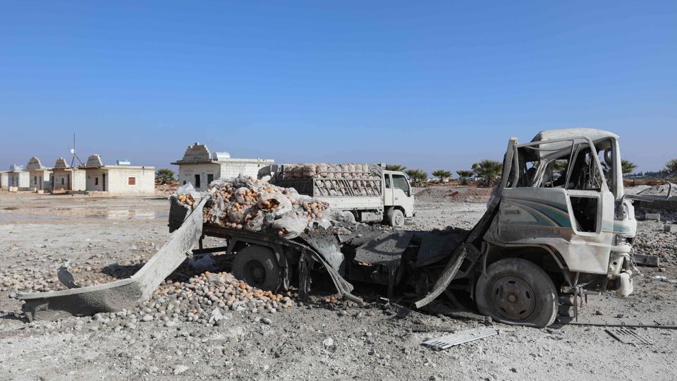 A picture taken on January 29 shows trucks loaded with sacks of potatoes standing abandoned after their windows were blasted from their frames following airstrikes by government forces which hit the vegetable market of the town of Saraqeb in Syria's northwestern province of Idlib.