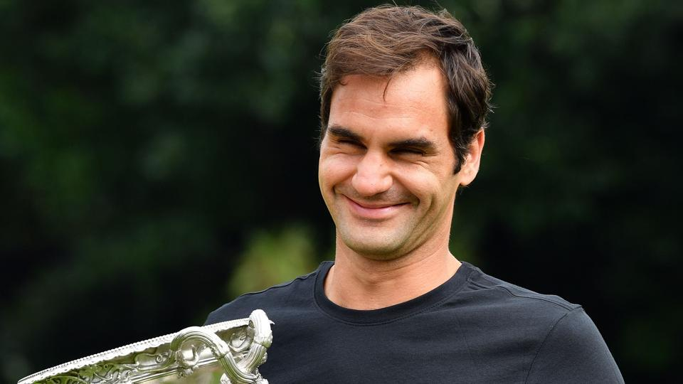 Switzerland's Roger Federer holds the Australian Open trophy at Government House as he poses for pictures following his win in Melbourne on Sunday.