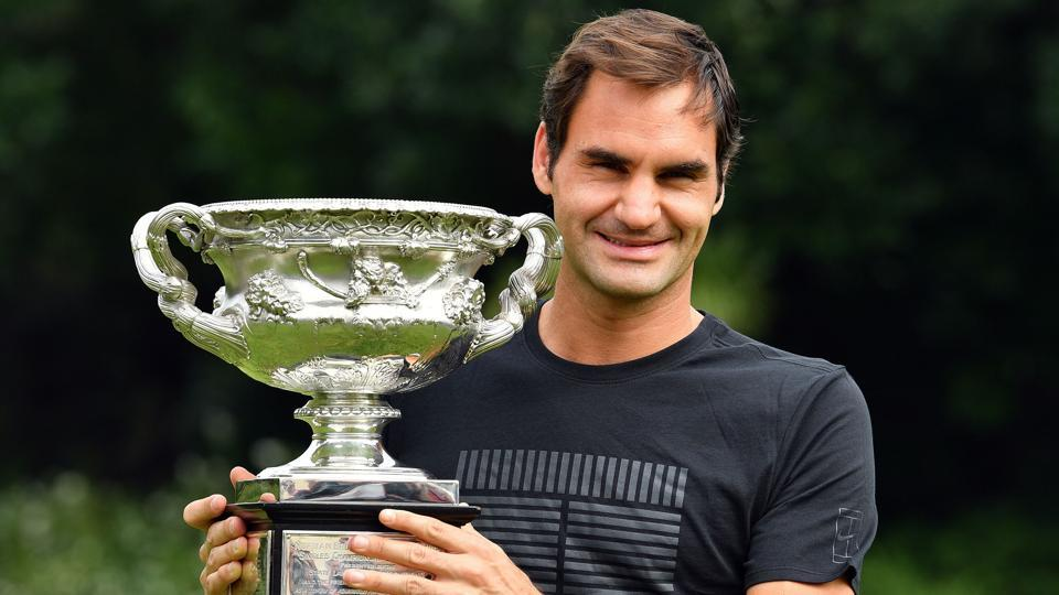 Switzerland's Roger Federer holds the Australian Open trophy at the Government House as he poses for pictures following his win in Melbourne on Sunday. (AFP)
