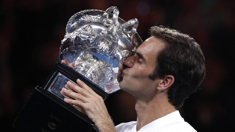 Switzerland's Roger Federer celebrates with the Australian Open trophy after winning the final against Croatia's Marin Cilic.