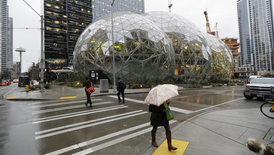 Pedestrians walk past the Amazon Spheres in downtown Seattle on the day of the opening of the geodesic domes which will serve as a working and gathering space for Amazon.com employees, on January 29, 2018. The structure, steps away from the office tower where Jeff Bezos leads the retail behemoth is part of the company's urban campus of unmarked office buildings where more than 40,000 people report to work. (Ted S. Warren / AP)