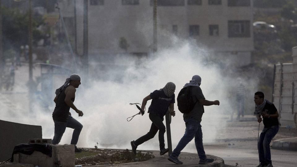 Palestinians run from tear gas during clashes with Israeli troops near Ramallah, West Bank, Monday, Oct. 12, 2015.