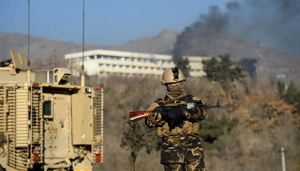 This file photo taken on January 21, 2018 shows Afghan security personnel standing guard as smoke billows from the Intercontinental Hotel during a fight between gunmen and Afghan security forces in Kabul.