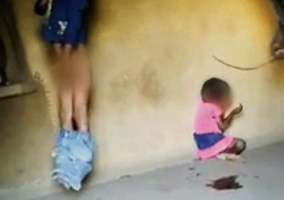 A screen grab from a video purportedly of Rajasthan man beating up his two small kids mercilessly with a stick. The  was circulating on social media.