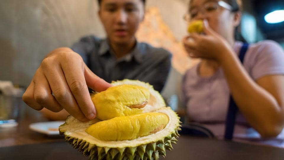 A customer reaching for durian at Mao Shan Wang café in Singapore.