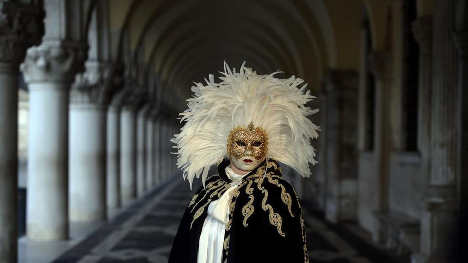 A masked reveller in a traditional carnival costume stands in St Mark Square. It was during the Renaissance that it became an official celebration, appealing to Italians because of the opportunities lent by the masks and parties to forget the rigid class system and the era's daily concerns. (Filippo Monteforte / AFP)