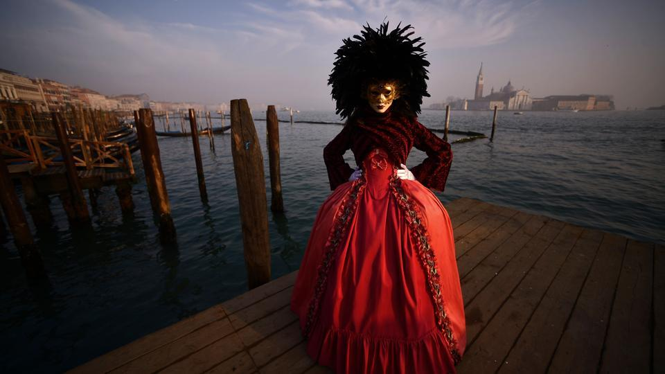 A masked reveller in a traditional carnival costume poses on the pier in St Mark Square during the opening of this year's Venice Carnival. The typically extravagant carnival that runs until Valentines' Day eve, kicked off on 27th January and will continue till 13th February just before Lent. (Filippo Monteforte / AFP)