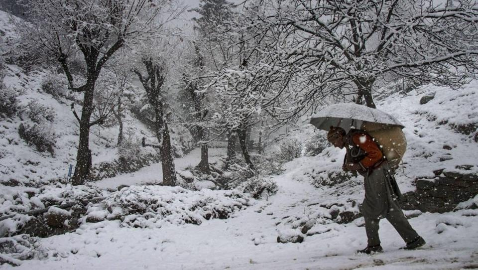 A man carrying a load on his back walks on a snow covered road in Baramulla district of Kashmir. An avalanche warning has been issued for several district.