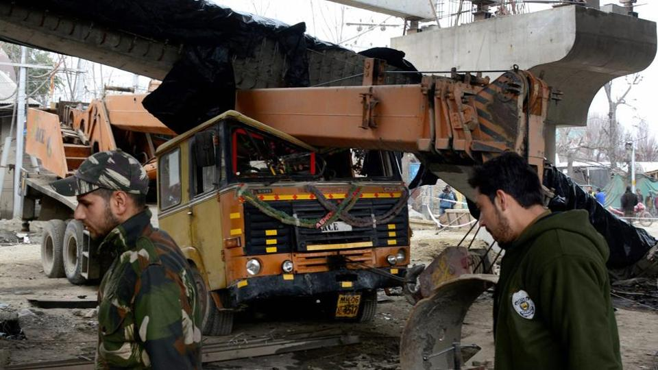 Police personnel inspect a girder of an under-construction flyover in Srinagar that collapsed after a 6.1 magnitude earthquake hit the city on Wednesday.