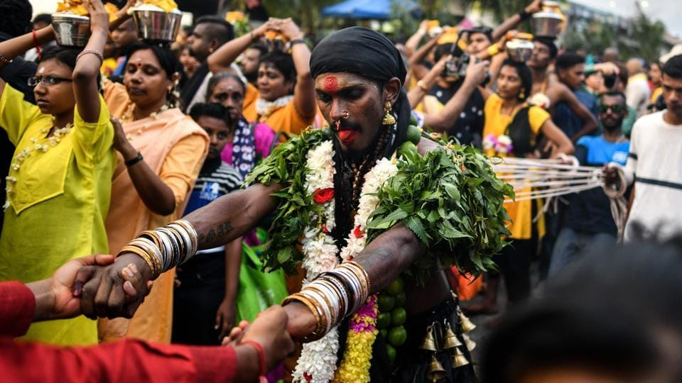 A devotee (C) is tied with ropes, hooked to his back as he dances in penance during Thaipusam celebrations in Kuala Lumpur. (Manan Vatsyayana / AFP)