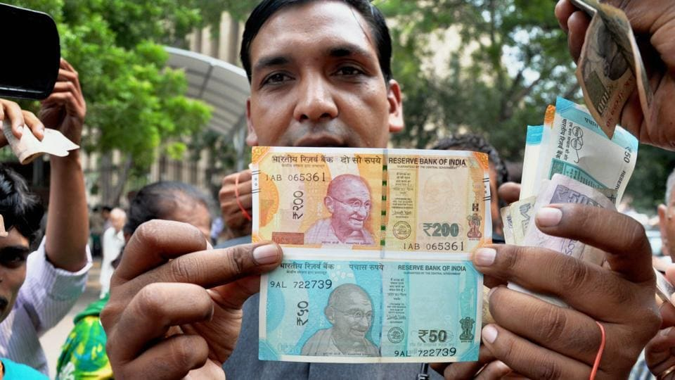 A man shows new currency notes of Rs 200 and Rs 50 outside the Reserve Bank of India in New Delhi on August 25, 2017.