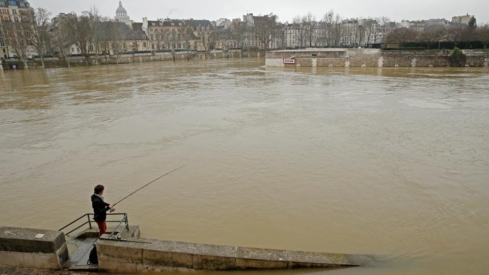 A man fishes on the flooded banks of the River Seine. Around 1,500 people have been evacuated from their homes in the greater Paris region while 1,900 households have lost electricity. Overall, Paris is better prepared than when it was last hit by floods in 2016, and Parisians have largely taken disruptions in stride. (Pascal Rossignol / REUTERS)