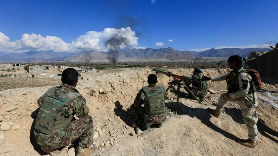 Afghan security forces take position during a gun battle with Taliban in Laghman province, Afghanistan.