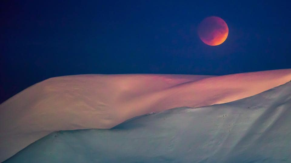 A super blue blood moon behind a mountain is seen from Longyearbyen, Norway. It was, as enthusiasts gushed, truly a once-in-a-blue- moon phenomenon, visible across several parts of the world. It's the first time in 35 years a blue moon has synced up with a supermoon and a total lunar eclipse, or blood moon because of its red hue. (NTB scanpix / Heiko Junge / AFP)