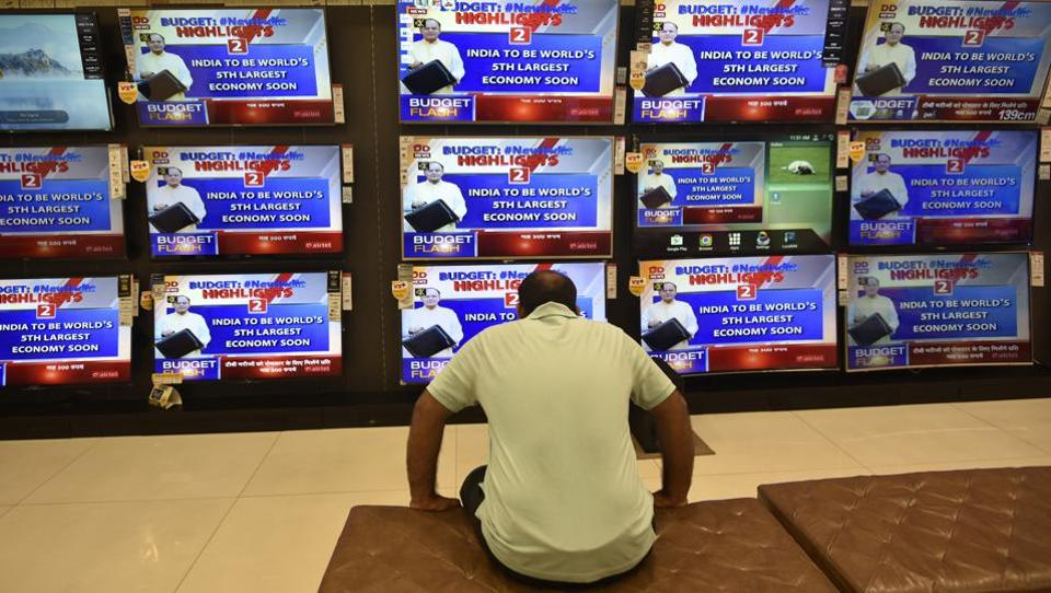 A man watches the live telecast of the Union Budget 2018 coverage on TV, in Mumbai on Thursday.