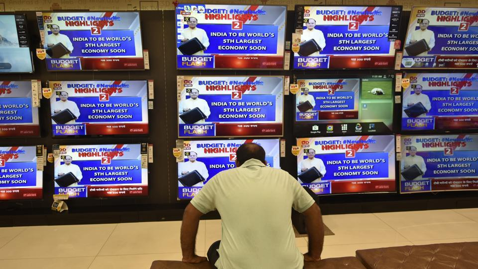 A man in Mumbai watches televisions playing Finance Minister Arun Jaitley presenting the union budget on Thursday, February 1.