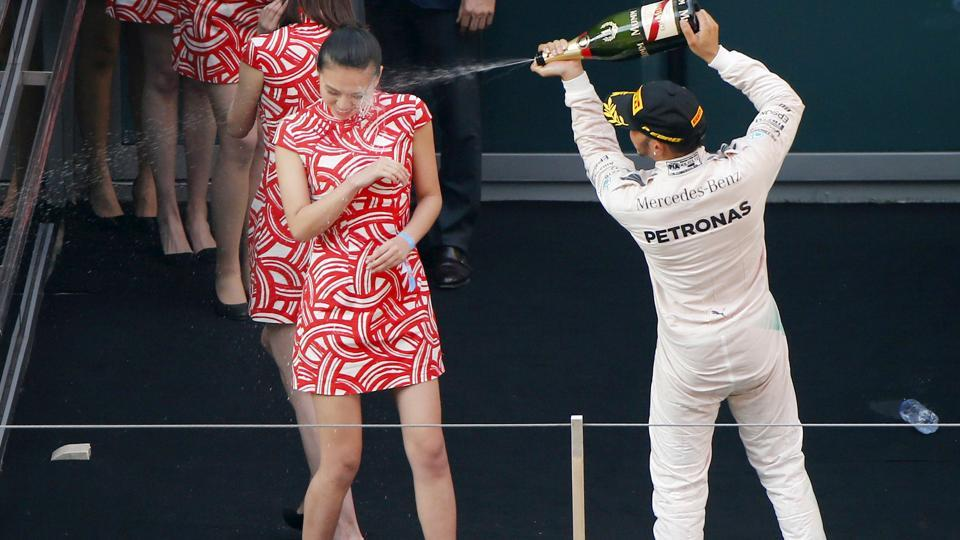 Mercedes Formula One (F1)driver Lewis Hamilton of Britain sprays champagne at a grid girl as he celebrates his victory on the podium after the Chinese F1 Grand Prix at the Shanghai International Circuit in this file picture. F1 has abolished grid girls from this season.
