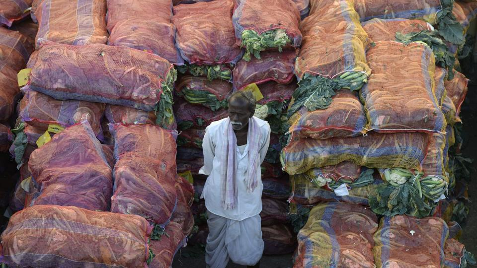 A farmer with his produce waits to negotiate with traders at a wholesale vegetable market in Hyderabad.