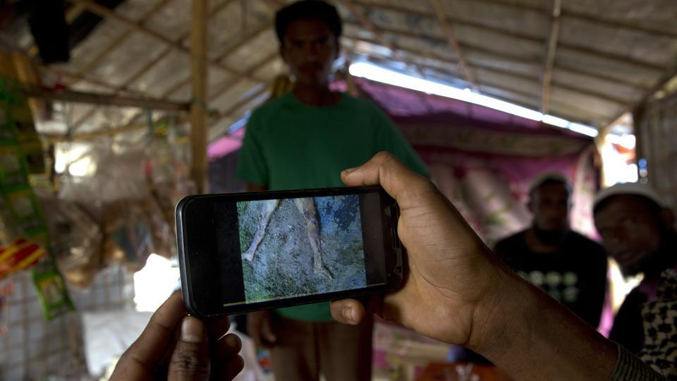 Mohammad Karim, a Rohingya Muslim refugee, shows a mobile video of Gu Dar Pyin's massacre inside his kiosk in Kutupalong refugee camp, Bangladesh.