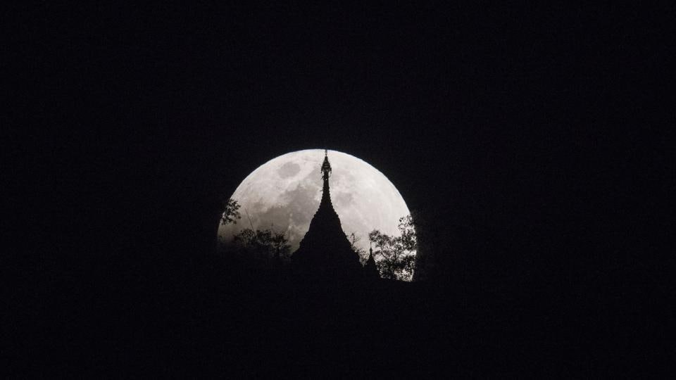 The moon rises over a pagoda in Kumal near Mandalay City. In Nepal, where the super moon was just visible in the hazy polluted sky over Kathmandu, the celestial phenomenon was greeted with more caution as an ominous sign. Local newspapers there had warnings telling citizens not to eat, drink, sleep or even go to the toilet during the eclipse, citing Hindu customs. (Ye Aung Thu / AFP)