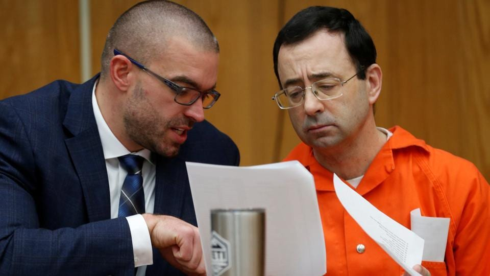 Larry Nassar, a former team USA Gymnastics doctor who pleaded guilty in November 2017 to sexual assault, talks with his attorney Matt Newburg during his sentencing hearing in the Eaton County Circuit Court in Charlotte, Michigan, on Wednesday.