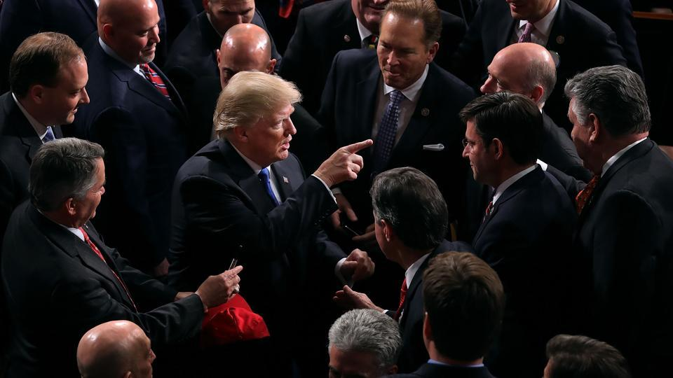 US President Donald Trump talks with members of Congress following the State of the Union address at the chamber of US House of Representatives in Washington DC.