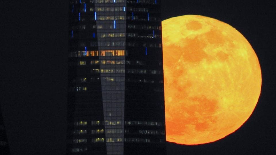 "A full moon ""supermoon"" rises next to a skyscraper in Madrid, Spain. NASA trained its instruments on the Lunar Reconnaissance Orbiter to measure the effect of the temperature drop during the one-hour-16-minute eclipse. Seeing what happens when the surface of the Moon cools quickly will help ""understand some of the characteristics of the regolith -- the mixture of soil and loose rocks on the surface -- and how it changes over time."" (Paul Hanna / REUTERS)"