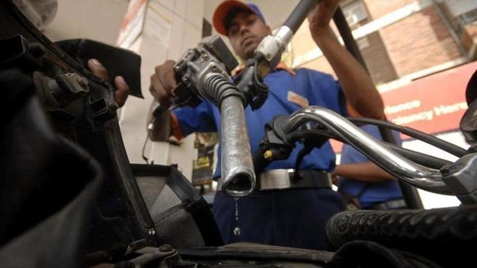A worker holds a fuel nozzle at a petrol pump in Hyderabad.