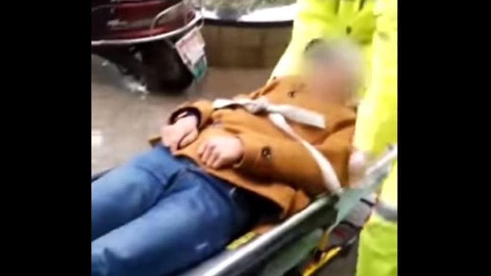Paramedics lift the man and secure him to a stretcher