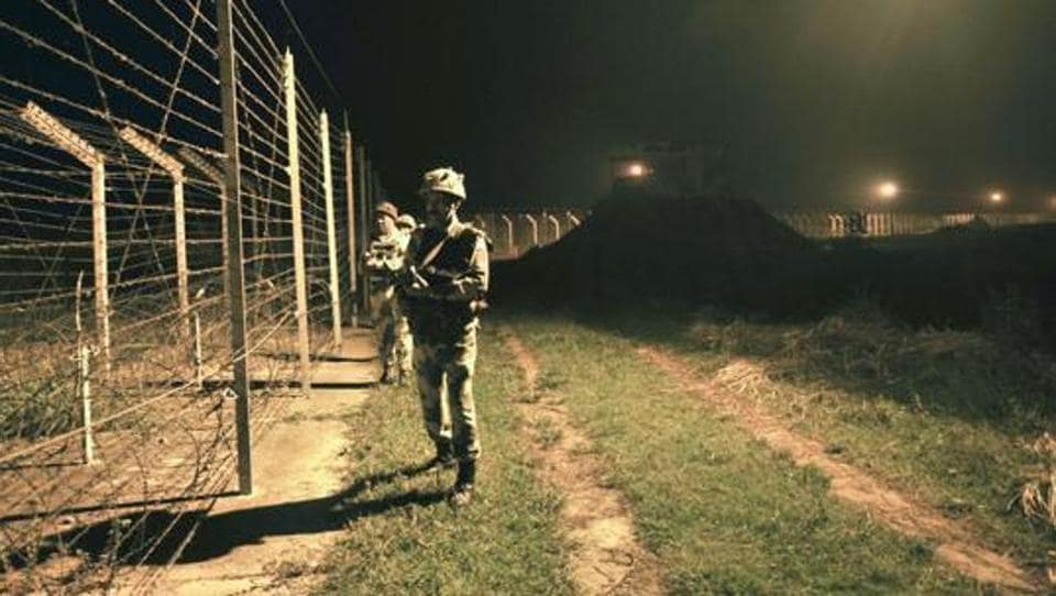 BSF personnel stand guard near the fence at the India-Pakistan border in Jammu region. (HT File Photo)