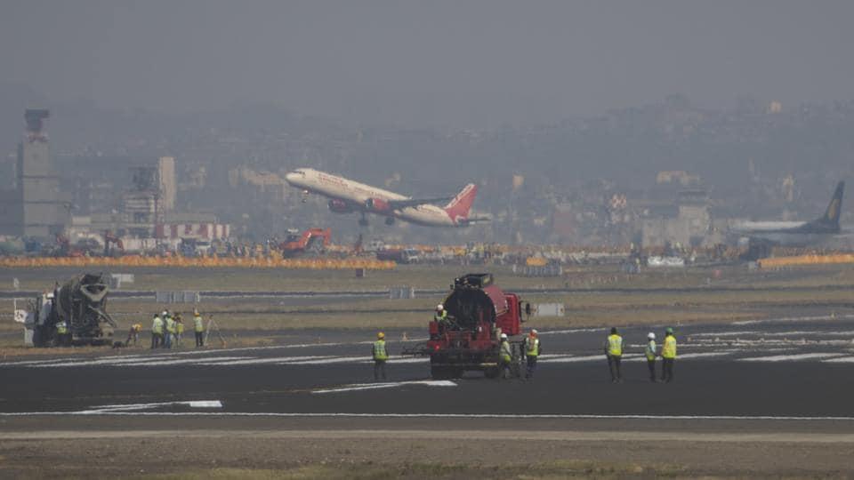Workers upgrade the Chhatrapati Shivaji InternationalAirport's main runway as flights operate from secondary one.