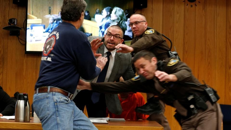Randall Margraves (L) lunges at Larry Nassar(wearing orange) a former team USA Gymnastics doctor who pleaded guilty to sexual assault charges at the Eaton County Circuit Court in Charlotte, Michigan.